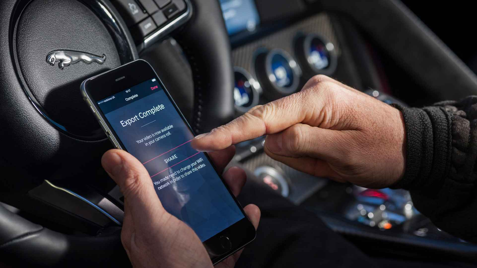 "Tapping an ""Export"" button on an iPhone, inside a Jaguar"