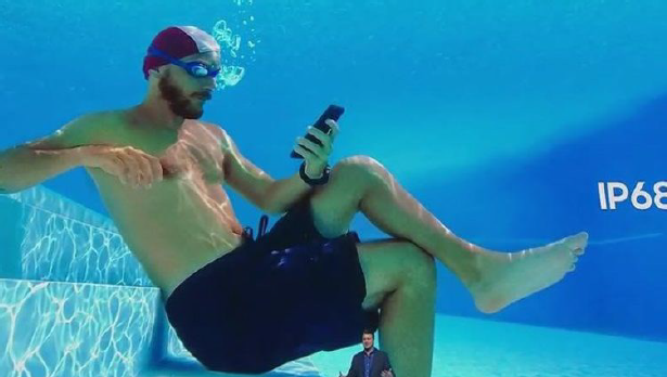 Man holding a phone underwater in a pool, as shown at a Samsung press event.