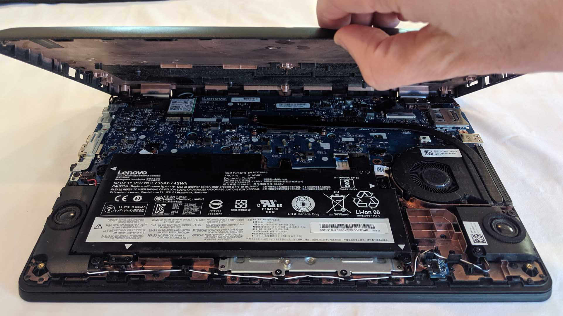 The bottom case of a laptop being removed.