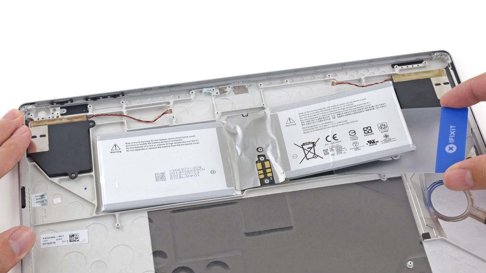 Removing the battery from a Surface Book display.