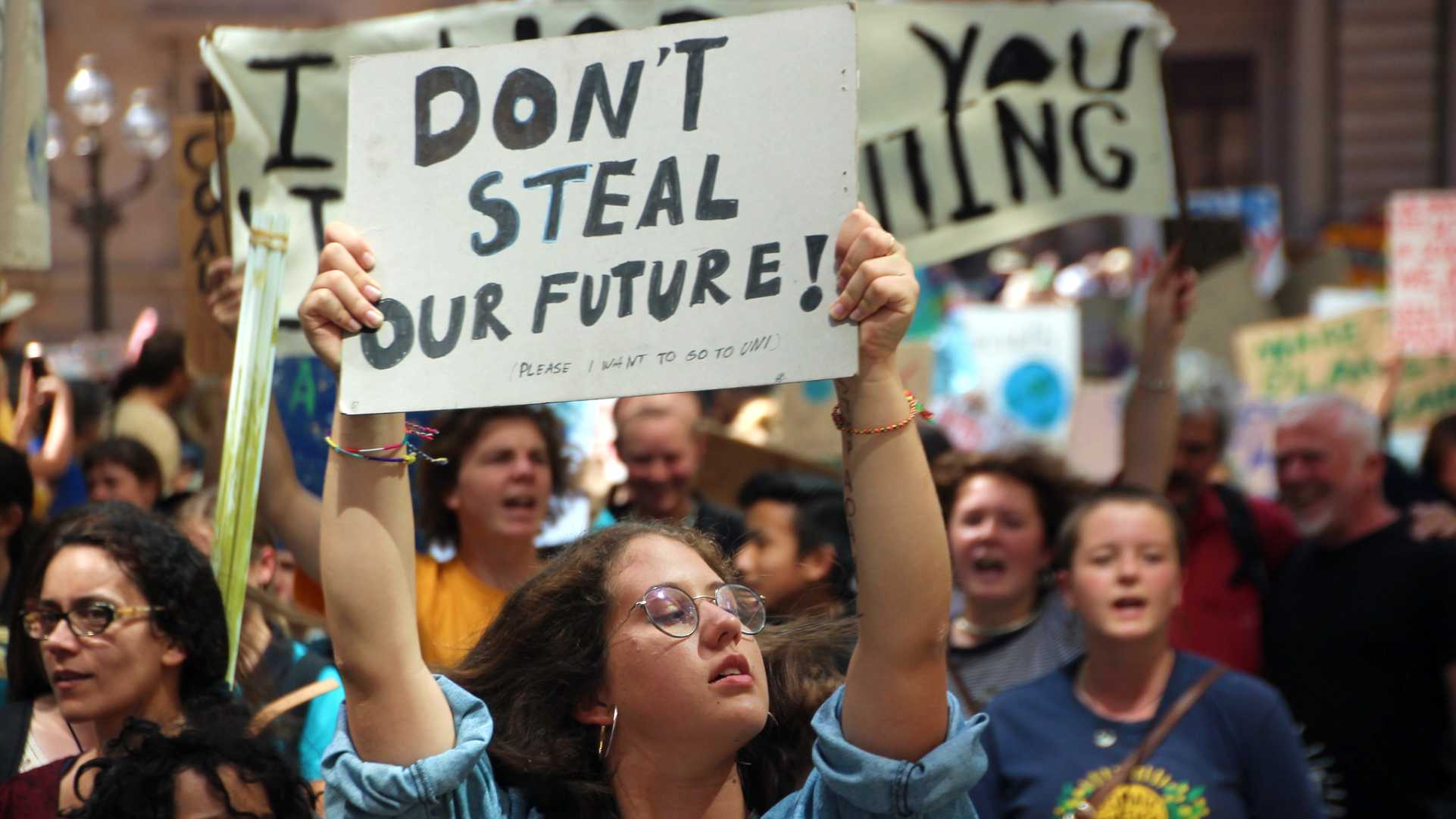 "Woman holding up a sign - ""Don't Steal Our Future"" - at Melbourne climate strike protest."