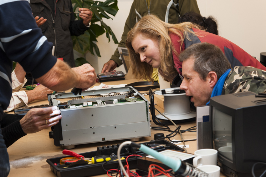 Repair Café visitors look at a broken item