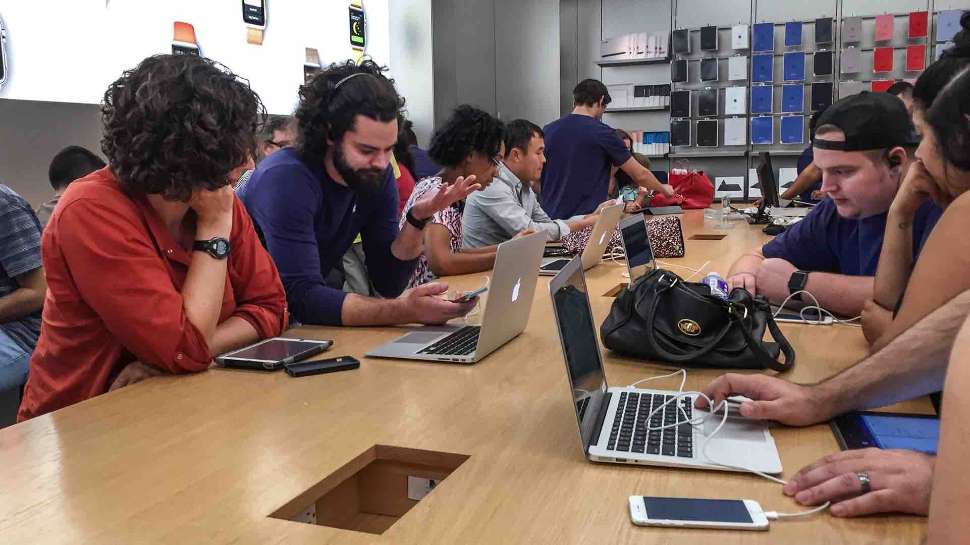Apple Store employees helping customers with devices