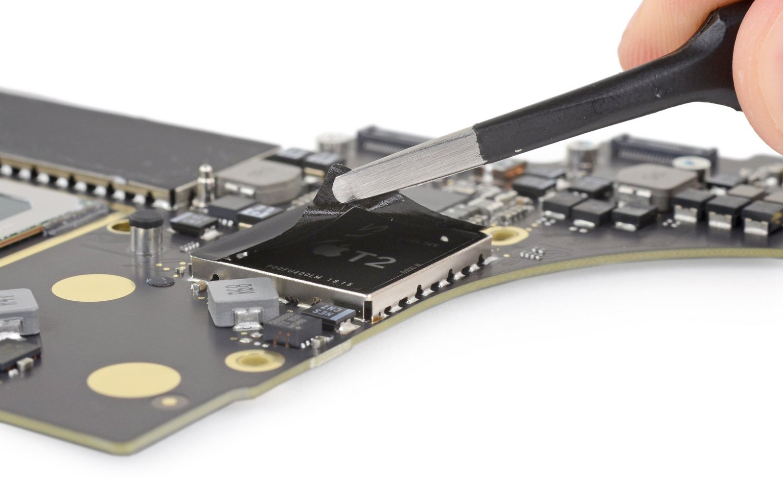 A pair of tweezers uncovering the T2 security chip on a MacBook Pro logic board.
