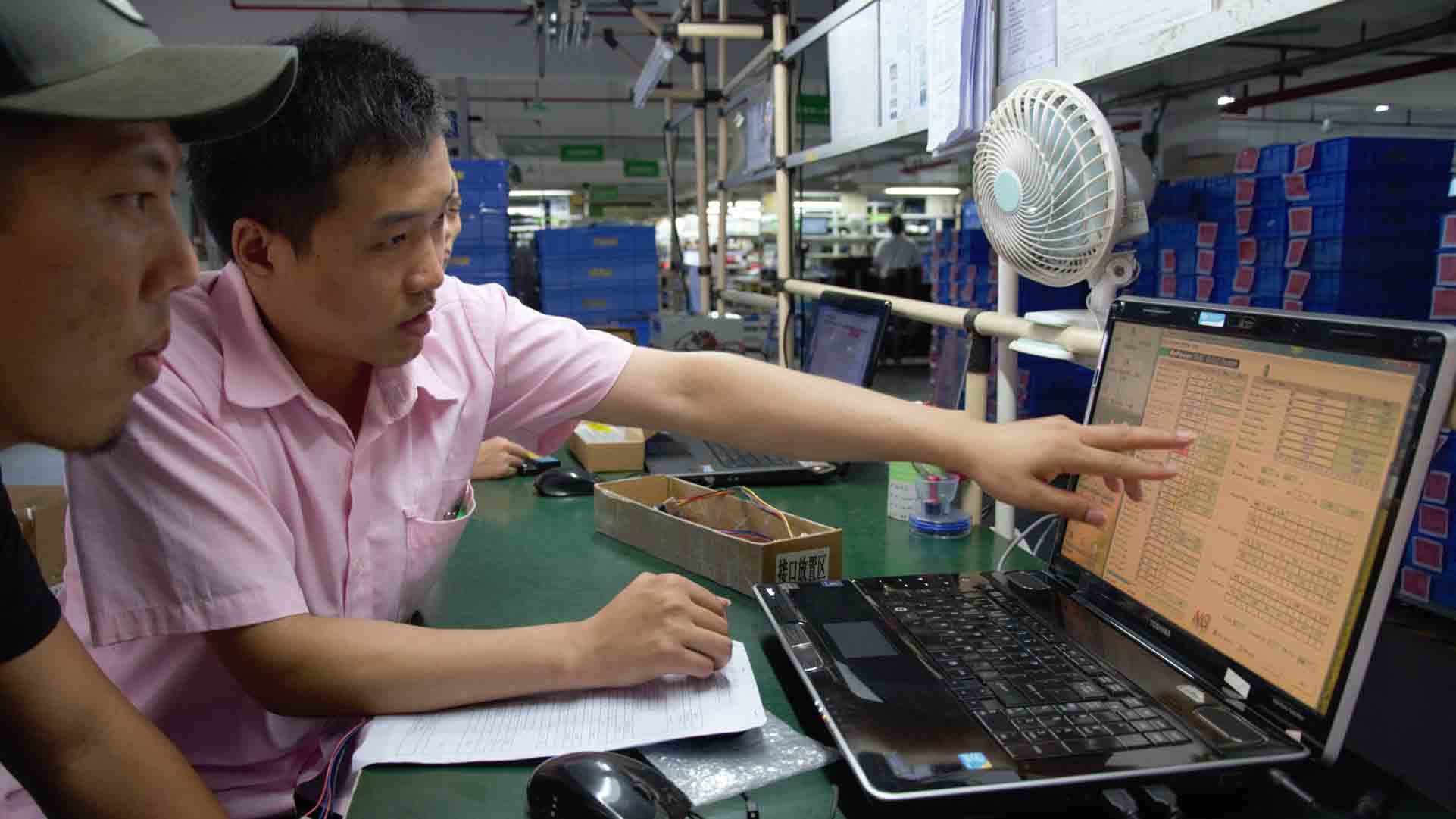 A man pointing to a laptop in a factory.