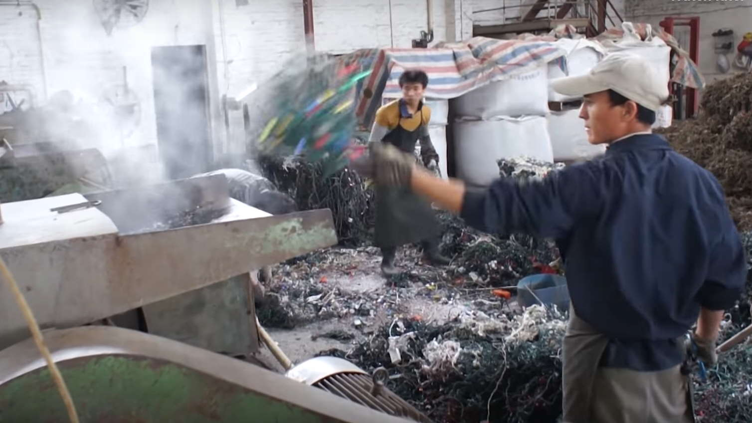 Image from video of workers in a Christmas light recycling plant in Shijao, China.