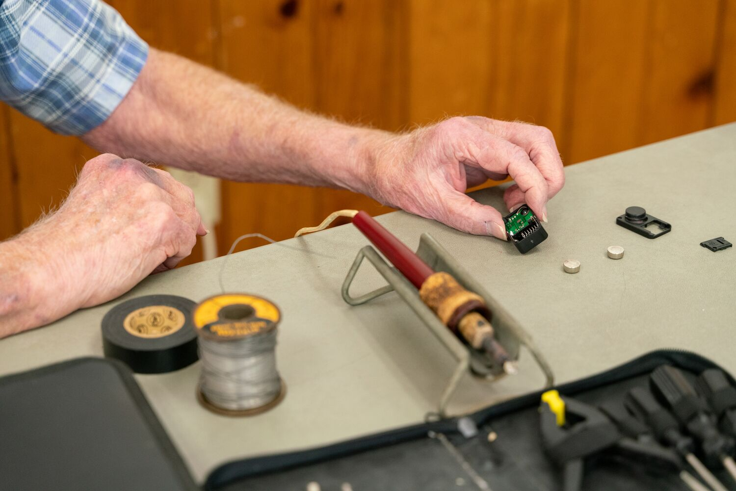 Man's hands holding a small electrical component at a repair cafe.