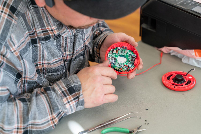 Examining a broken-open device at a repair cafe