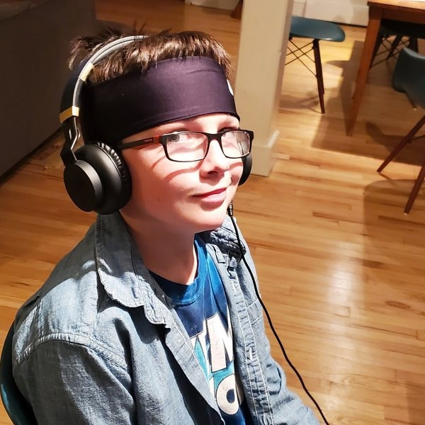 Young boy wearing a gaming hedset, looking at the camera askew