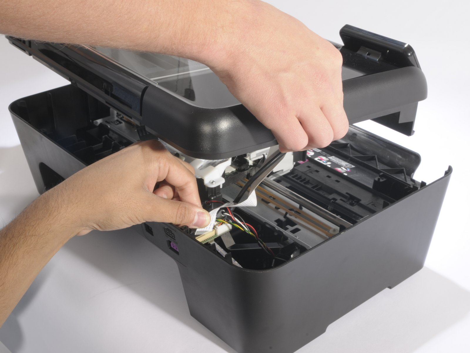 Two hands disassembling scanner hood on an all-in-one printer.