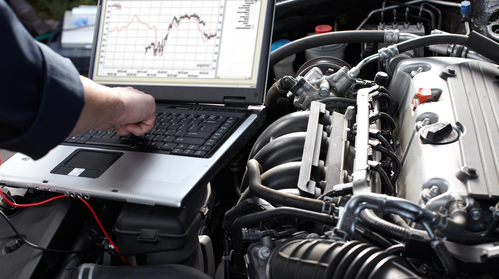 Laptop perched on a car engine