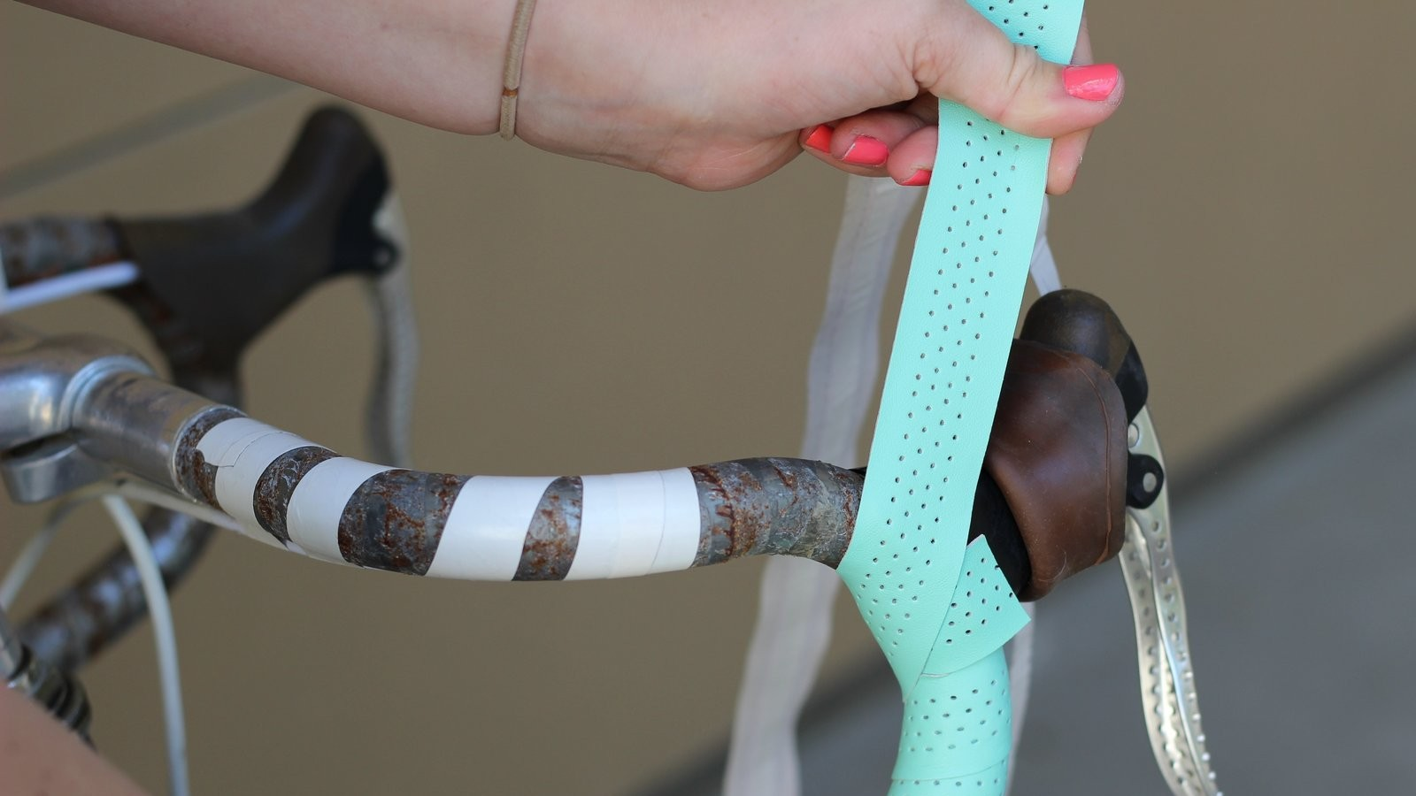 Wrapping aqua-green bar tape around a handlebar.