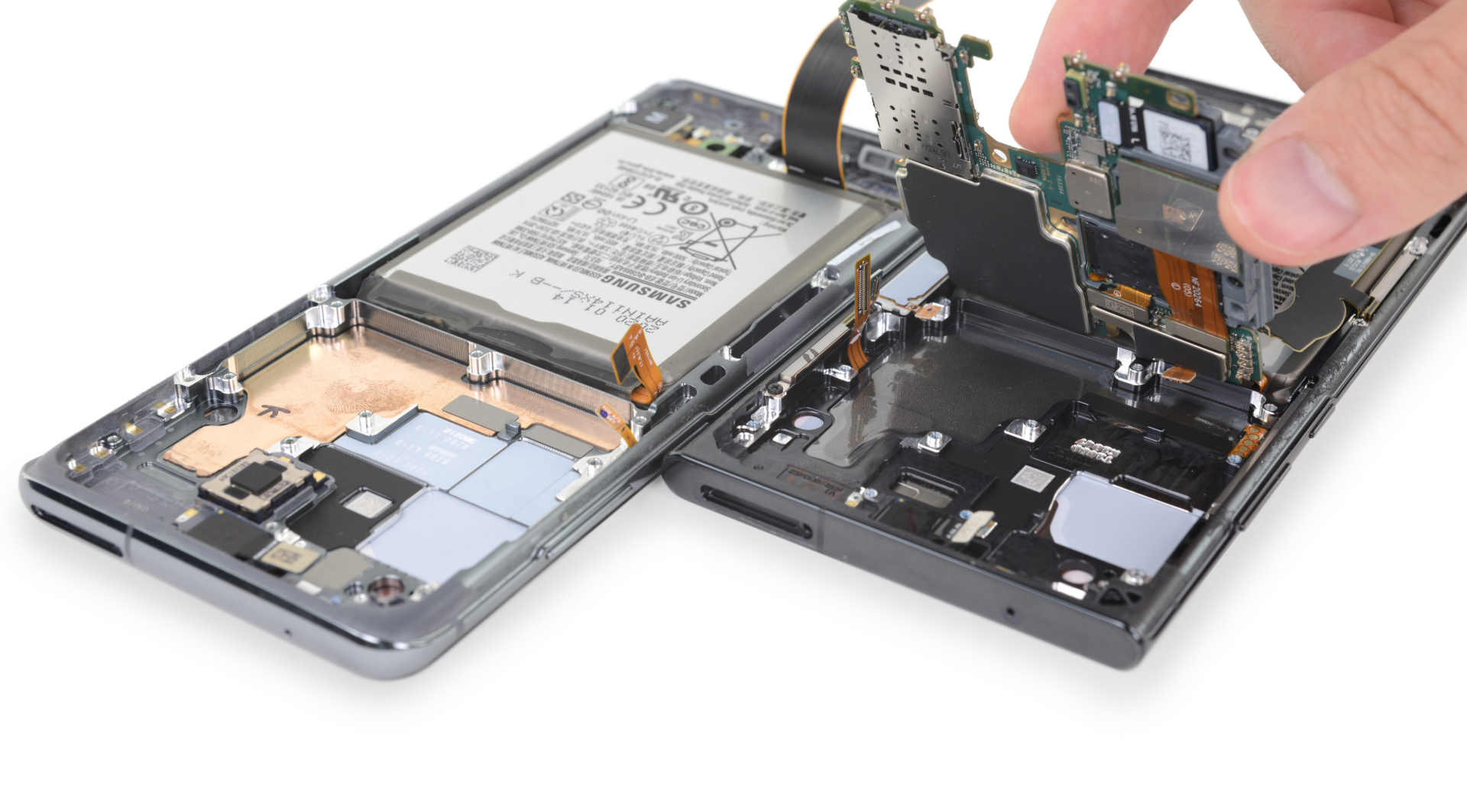 Pulling up the motherboard from a Galaxy Note 20, with graphene cooling pads.