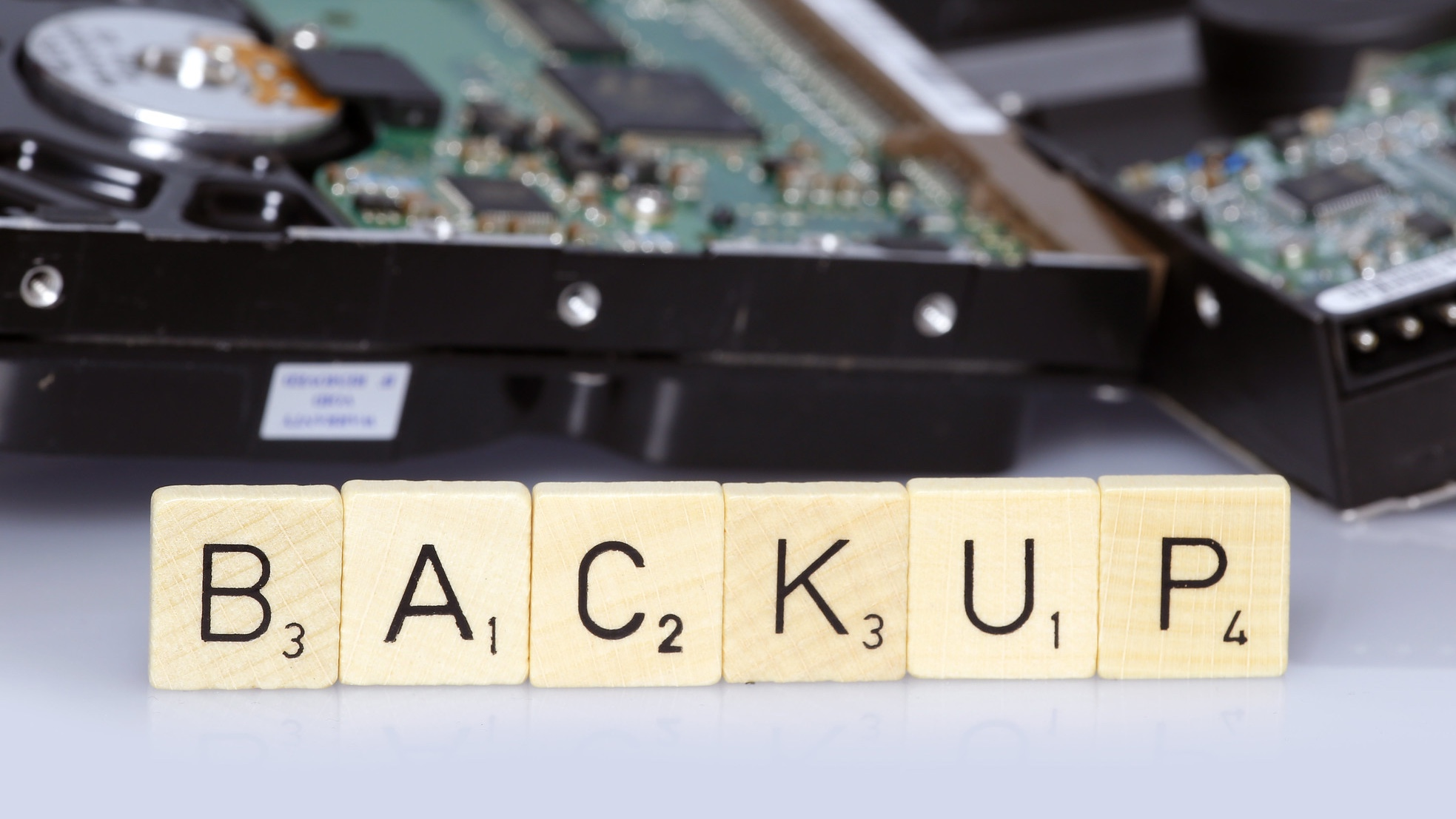 """Hard drive disassembled, with """"BACKUP"""" spelled in Scrabble tiles in foreground."""
