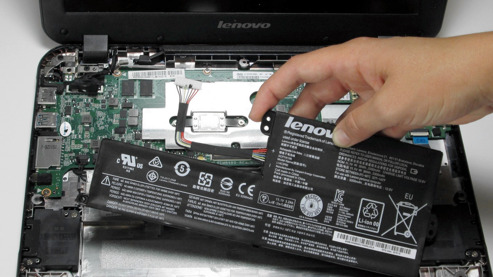 Hand removing the battery from an N21 Lenovo Chromebook