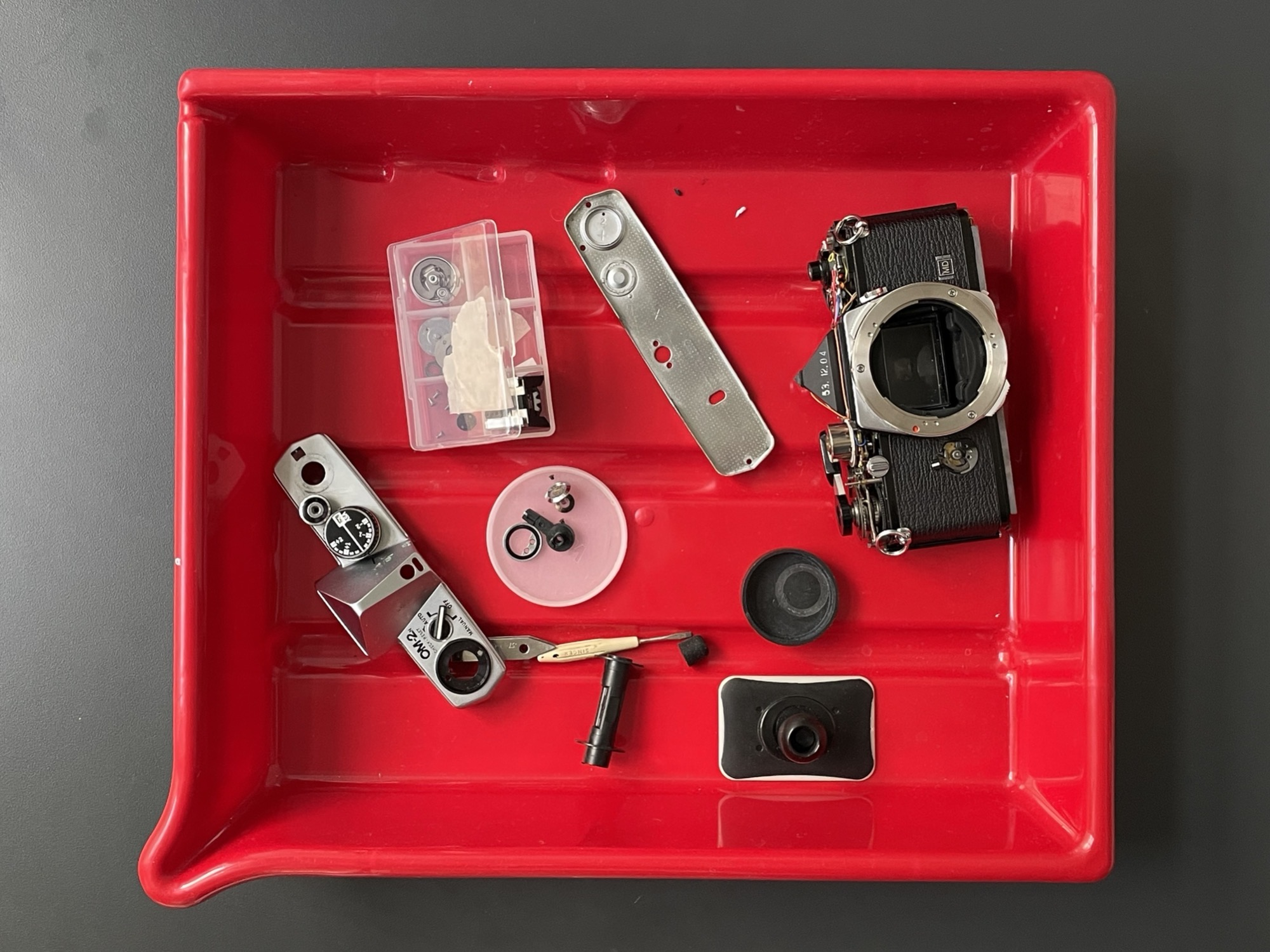 Olympus OM-2n, disassembled and parts in a red bucket.