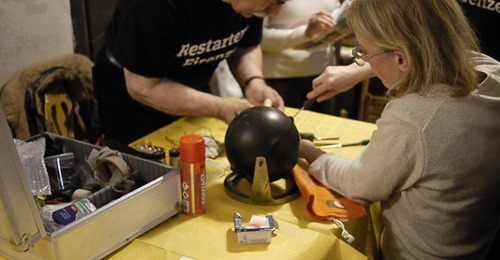 Two repair cafe workers fixing a block round objects