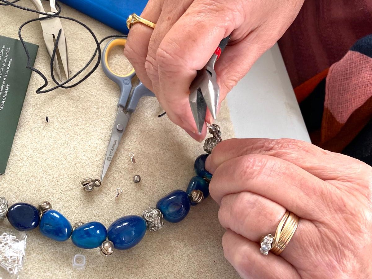 Hands using pliers to repair jewelry.