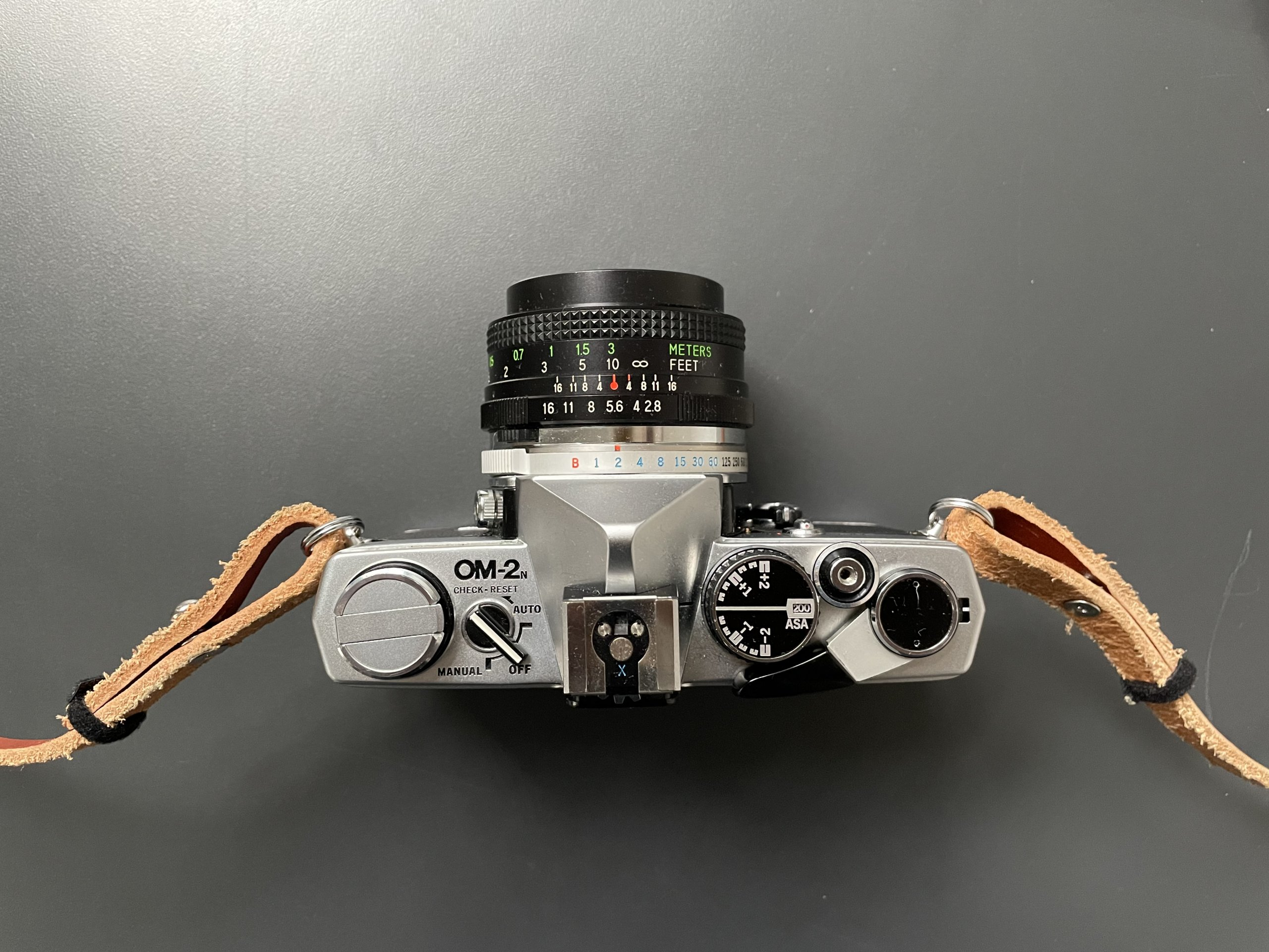 Olympus OM-2n camera, from the top, on a gray steel table.