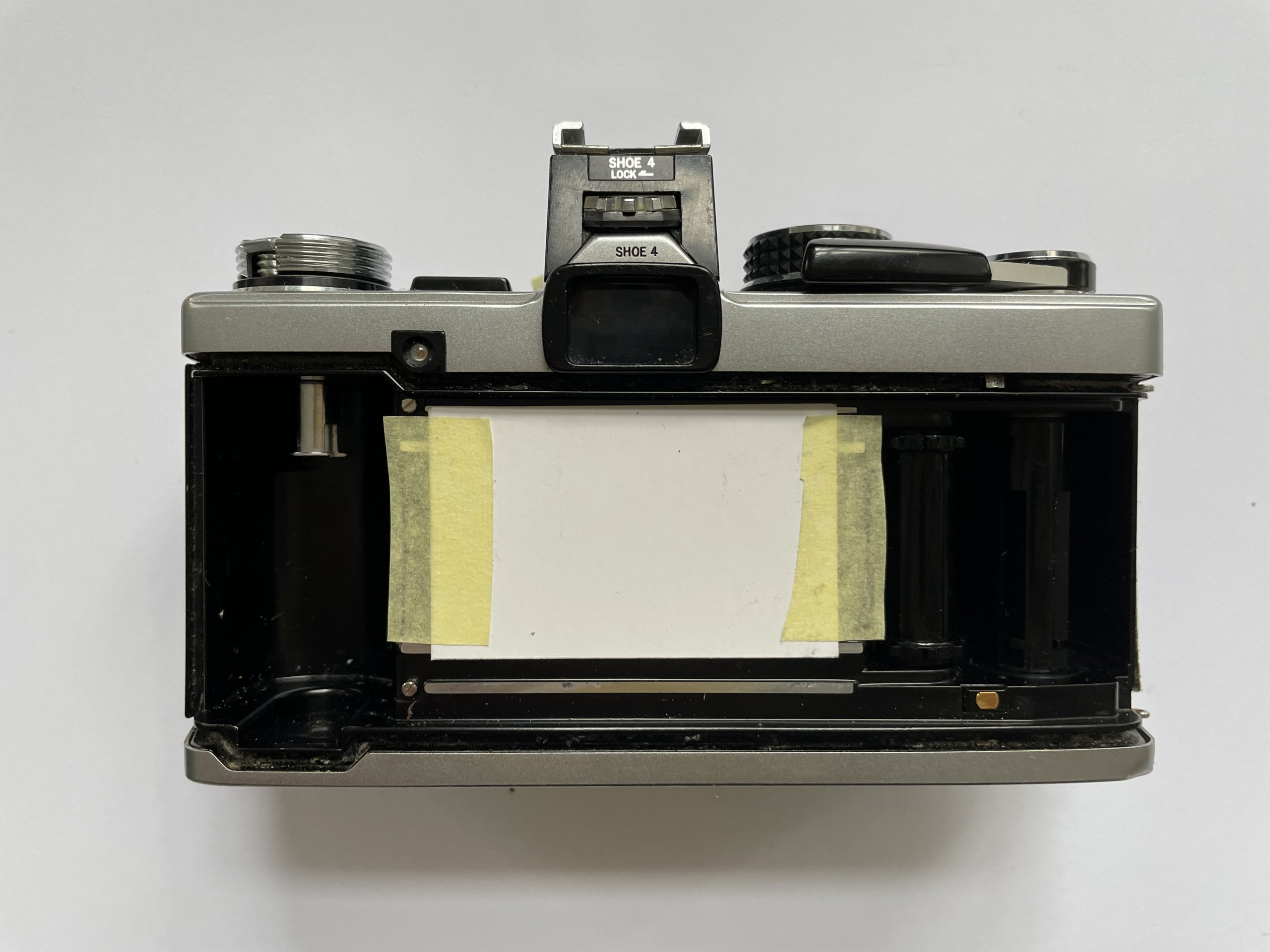 Film camera with door removed, replaced with taped-down index card