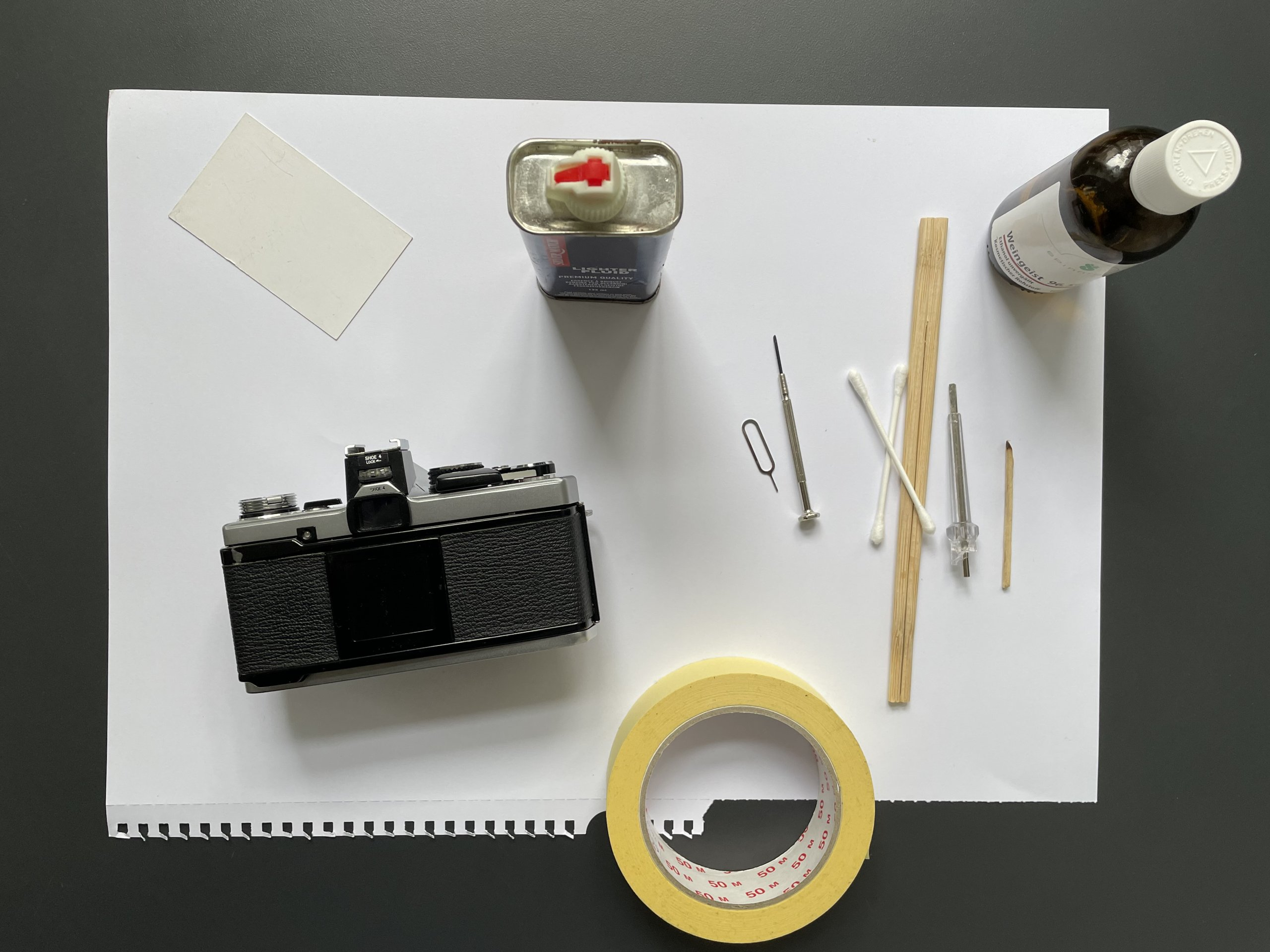 Camera, lighter fluid, and tools for removing foam, laid out on table