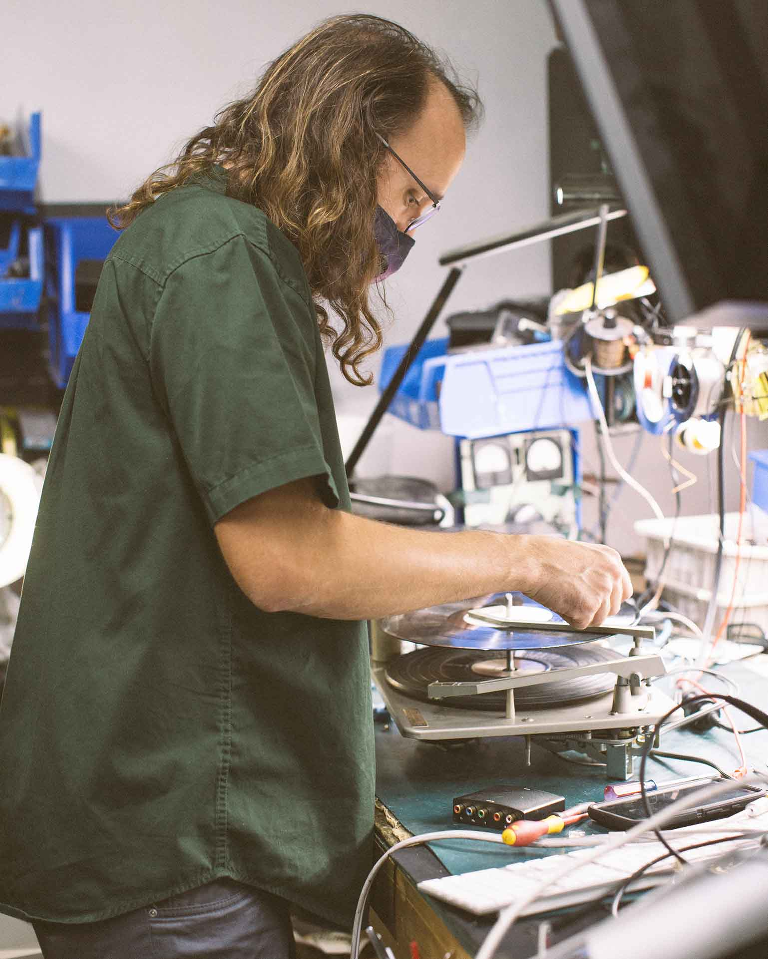 Brian Fox, head of reuse at Homeboy Electronics Recycling, works on a broken record player.