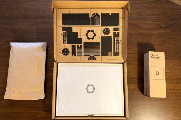 Framework laptop, box lid removed, with power adapter and parts nearby