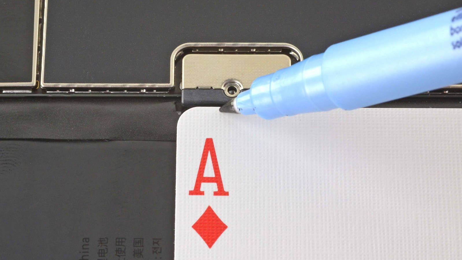 Playing card lined up with battery connector and marker.