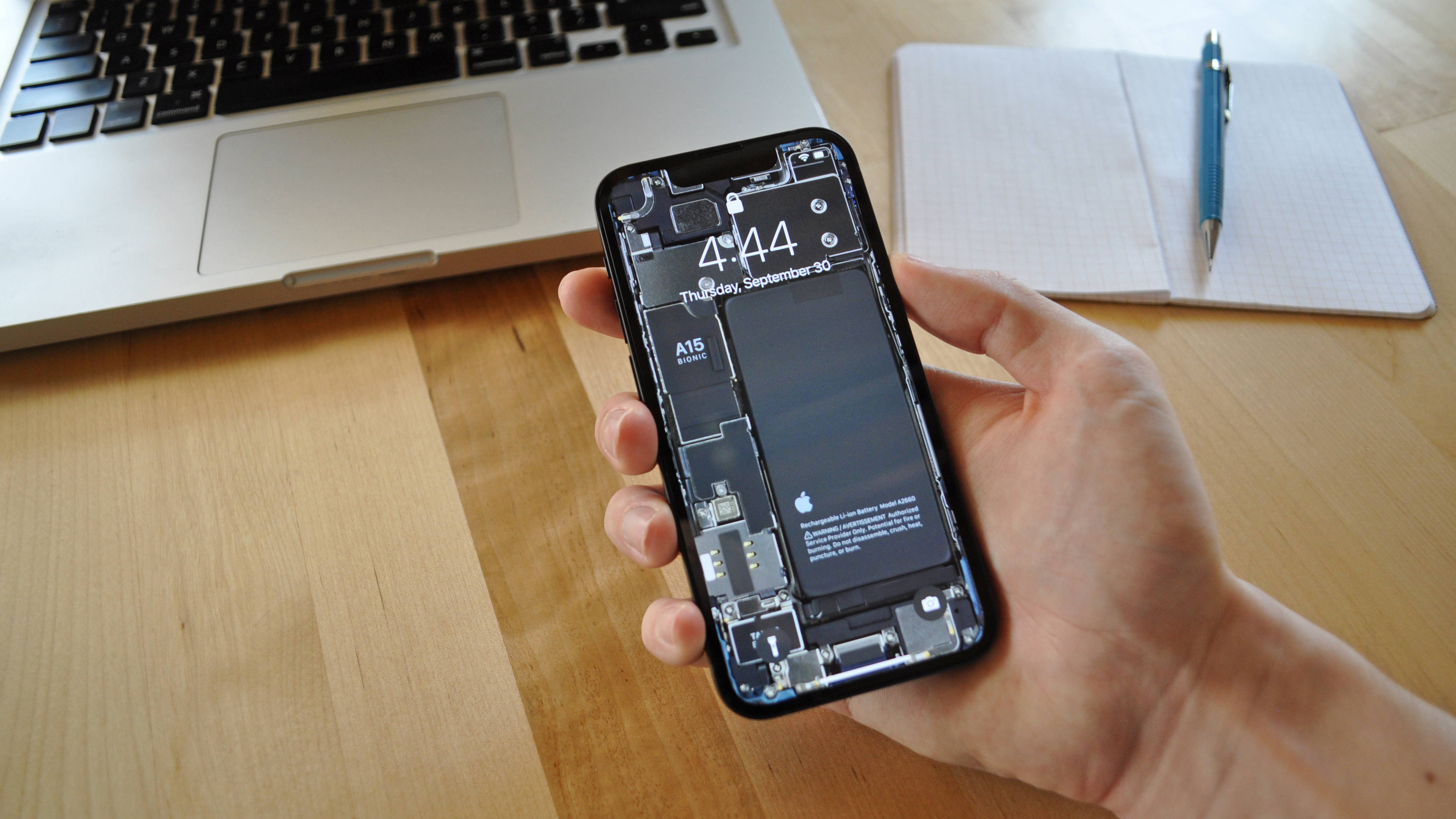 An iPhone 13 mini with internals wallpaper applied is held over a desk containing a MacBook and a notebook with pencil.